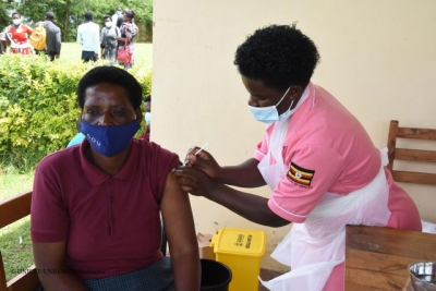 A health worker vaccinating a lady